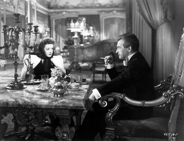Medium shot of Bette Davis as Christine Radcliffe and Claude Rains as Alexander Hollennius, seated at table.