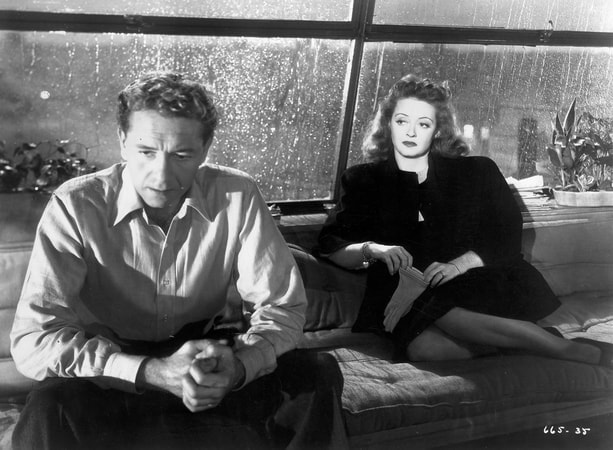 Medium shot of Paul Henreid as Karel Novak and Bette Davis as Christine Radcliffe, seated on couch/sofa.