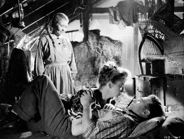 Medium shot of Fay Bainter as Ellie Saul, standing, looking down at Ida Lupino as Libby Saul embracing Dane Clark as Barry Burnette.