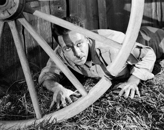 Medium shot of Dane Clark as Barry Burnette couching behind wagon wheel.