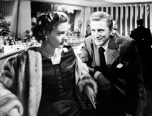 Medium shot of Lauren Bacall as Amy North with fur and cigarette sitting at bar next to Kirk Douglas as Rick Martin.