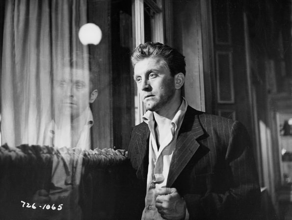 Medium shot of Kirk Douglas as Rick Martin staring blankly into a window