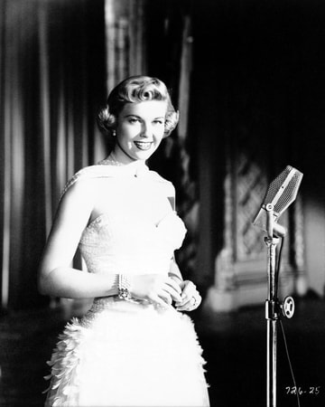 Medium shot of Doris Day as Jo Jordan wearing a white gown standing at microphone.