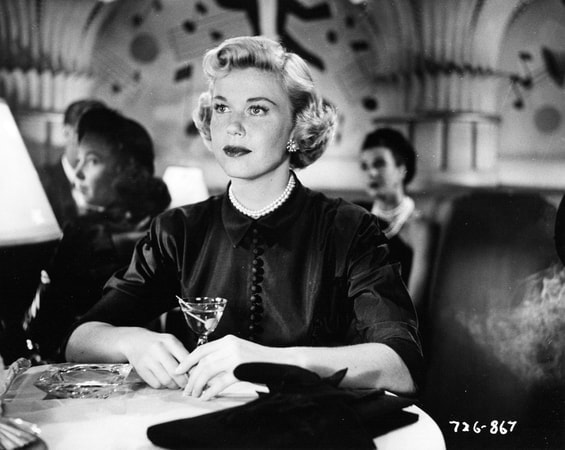 Medium shot of Doris Day as Jo Jordan sitting at a nightclub table wearing a black dress and pearls holding a martini