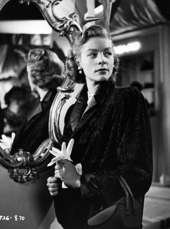 Medium shot of Lauren Bacall as Amy North holding white gloves, standing in front of mirror