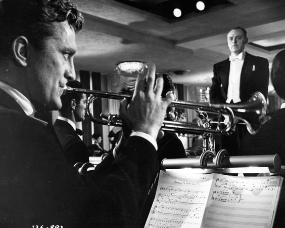 Medium shot of Kirk Douglas as Rick Martin playing trumpet.