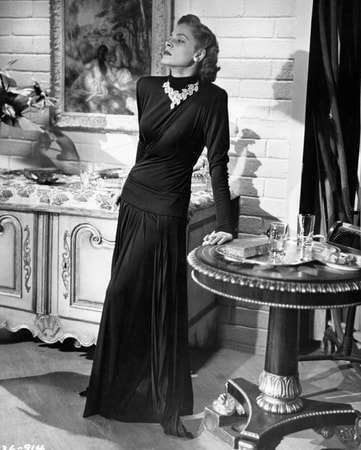 Medium shot of Lauren Bacall as Amy North in a long dark gown