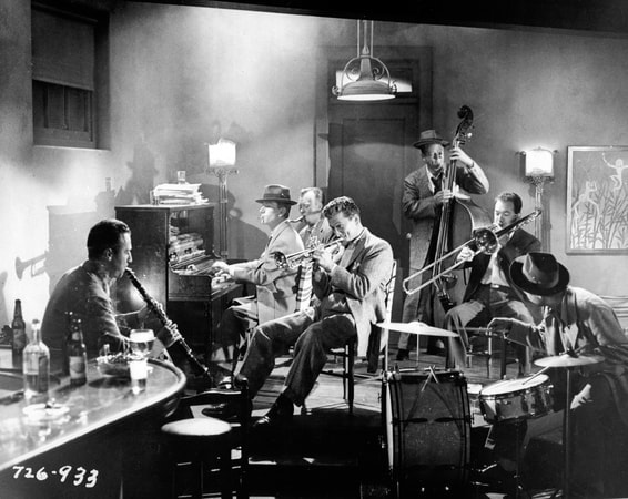 Medium shot of Kirk Douglas as Rick Martin playing trumpet with a group of musicians