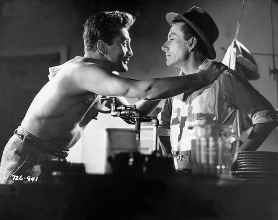 Medium shot of shirtless Kirk Douglas as Rick Martin shirtless standing next to a bar tender