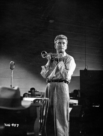 Medium shot of Kirk Douglas as Rick Martin playing trumpet in a practice space for musicians
