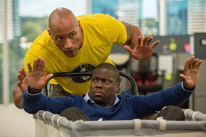 KEVIN HART as Calvin in a laundry transport and DWAYNE JOHNSON as Bob behind him