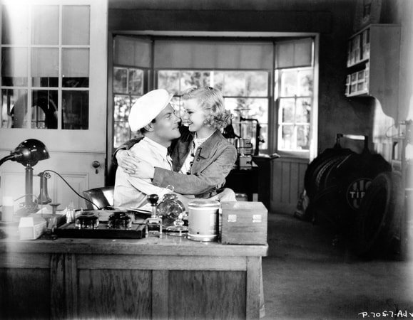 Medium shot of Joel McCrea as Blacky Gorman with hat sitting at desk with Marian Nixon as Glory Franklyn sitting in his lap arms around him.