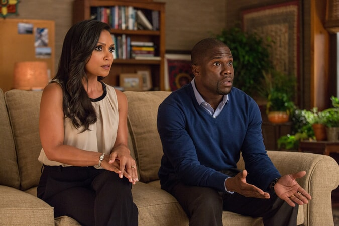 DANIELLE NICOLET as Maggie and KEVIN HART as Calvin sit next to each other on a couch