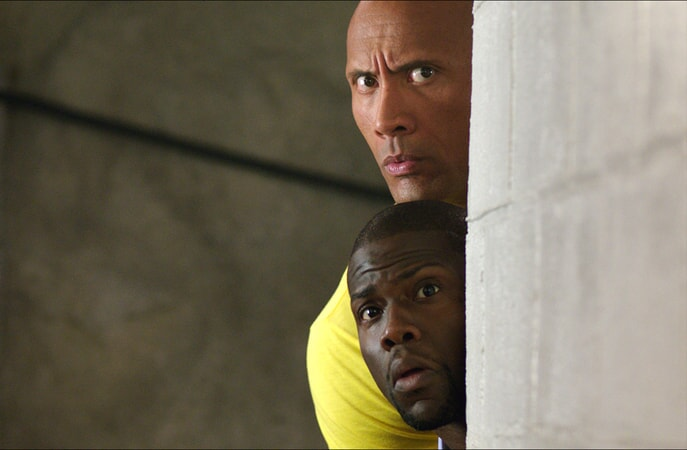 DWAYNE JOHNSON as Bob and KEVIN HART as Calvin peer out from behind a column
