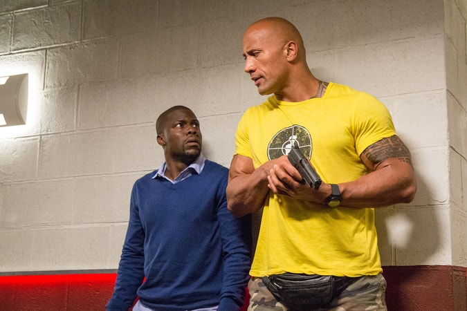 KEVIN HART as Calvin and DWAYNE JOHNSON as Bob (holding a gun)