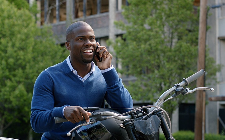 KEVIN HART as Calvin sitting on a motorcycle and talking on a cell phone