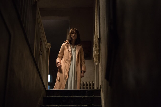 FRANCES O'CONNOR as Peggy Hodgson standing at top of staircase in night clothes