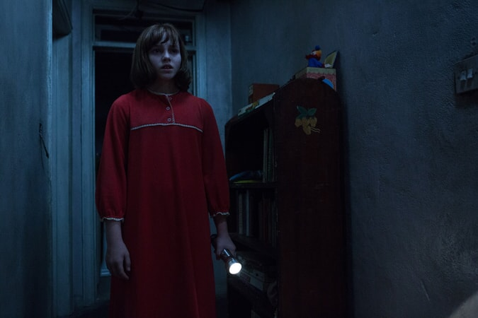 MADISON WOLFE as Janet Hodgson wearing a red nightgown and holding a flash light