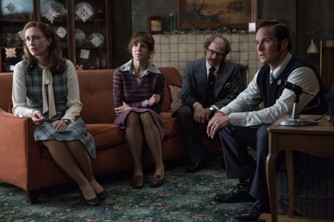 VERA FARMIGA as Lorraine Warren, FRANCES O'CONNOR as Peggy Hodgson, SIMON McBURNEY as Maurice Grosse and PATRICK WILSON as Ed Warren sitting together in a semi-circle on orange sofas