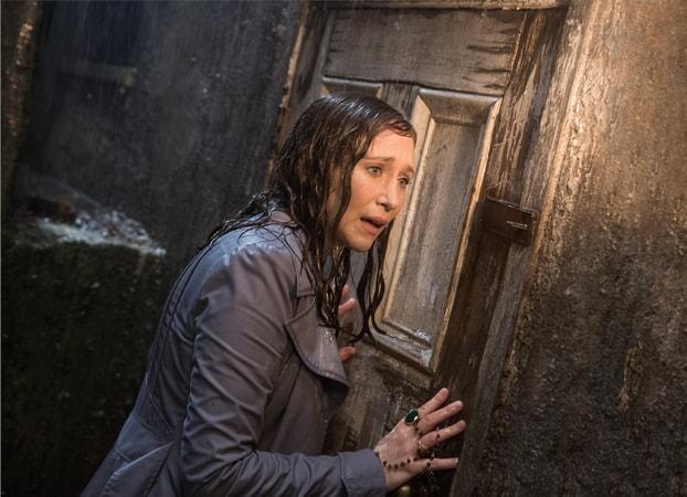 VERA FARMIGA as Lorraine Warren soaking wet standing up against a wooden door