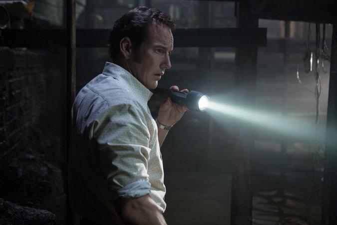 PATRICK WILSON as Ed Warren holding a lit flashlight in the dark