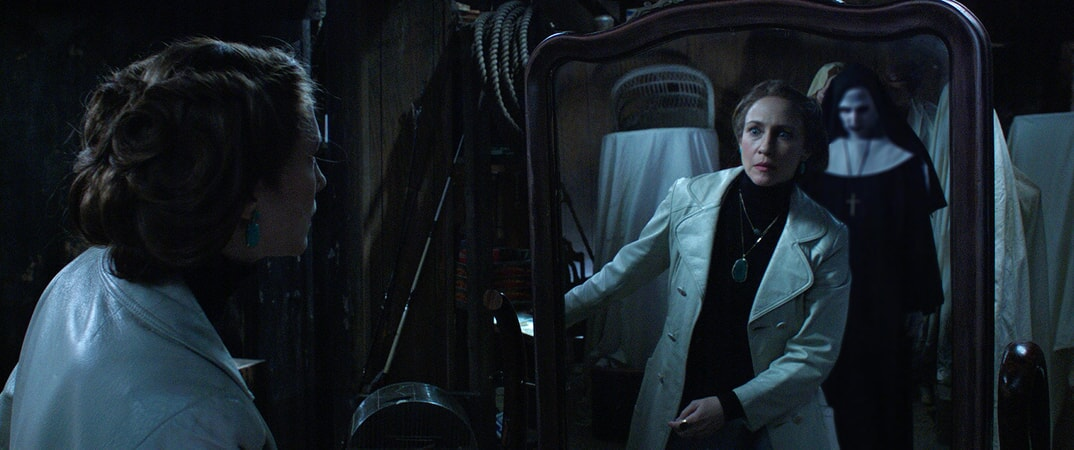 VERA FARMIGA as Lorraine Warren looking in mirror with ghostly nun showing its reflection