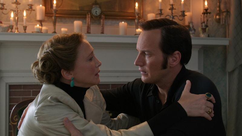 VERA FARMIGA as Lorraine Warren and PATRICK WILSON as Ed Warren holding each other by the shoulders with lit candles in background