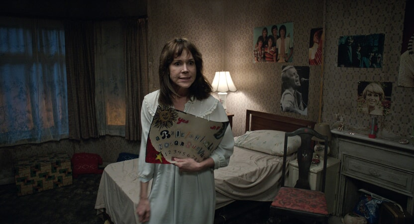 FRANCES O'CONNOR as Peggy Hodgson holding a Ouija board with an angry expression on her face