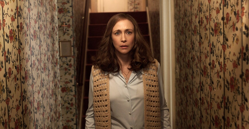 VERA FARMIGA as Lorraine Warren standing in front of a staircase wearing a crocheted sweater vest