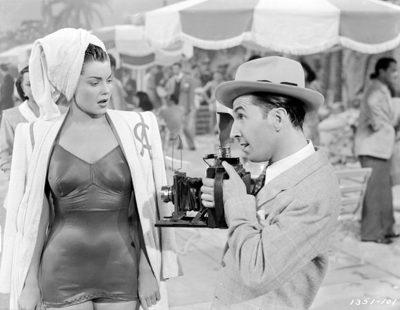 Eshter Williams as Connie Allenbury with towel on head standing facing Ben Blue as Spike Dolan with hat holding camera.