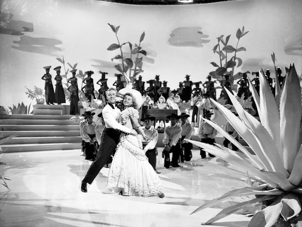 Wide angle shot of Esther Williams as Connie Allenbury with hat on stage with Van Johnson as Bill Chandler and dancers behind them.