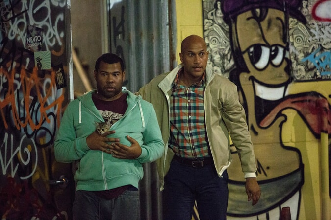 JORDAN PEELE as Rell, holding Keanu the kitten in his sweatshirt and KEEGAN-MICHAEL KEY as Clarence, walking through the street with graffiti in background