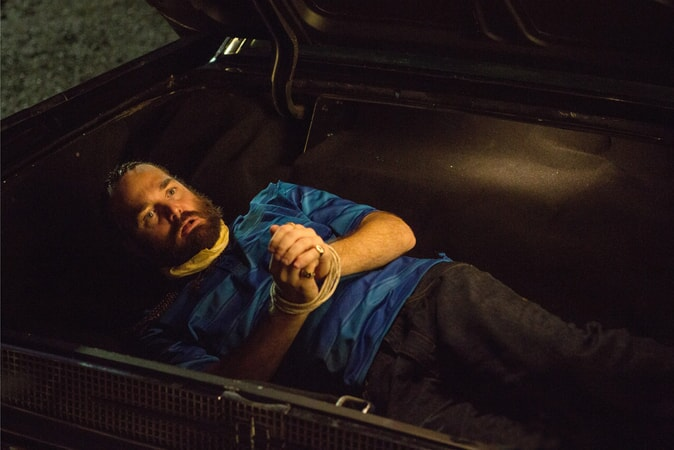 WILL FORTE as Hulka with wrists tied with rope in trunk of car