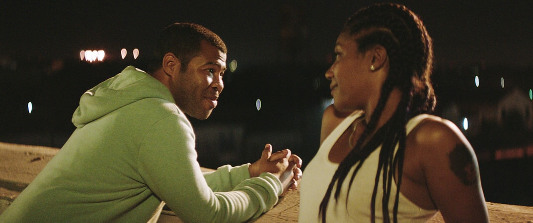 JORDAN PEELE as Rell and TIFFANY HADDISH as Hi-C having a conversation outside at night