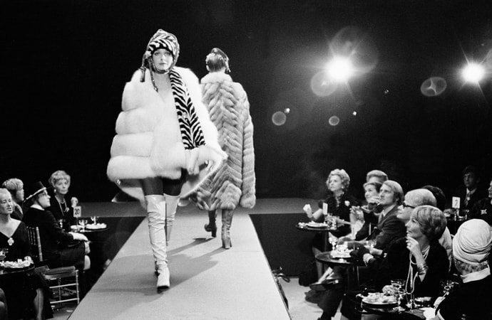 Full shot of models wearing fur coats on runway of fashion show, with audience looking on.