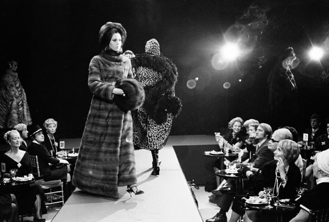 Full shot of Jane Fonda as Bree Daniel wearing fur coat and hat, and other model, on runway of fashion show, with audience looking on.