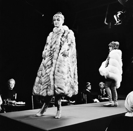 Full shot of models wearing fur coats on runway of fashion show, with audience looking on