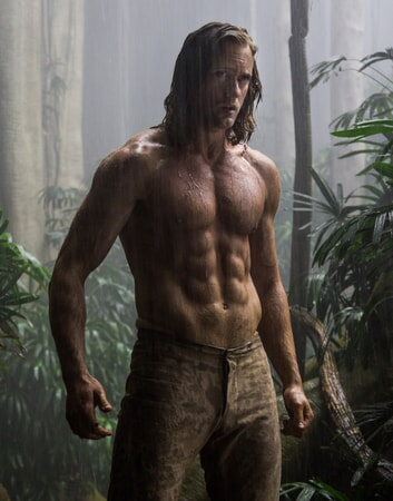 Shirtless Alexander Skarsgård as Tarzan standing in the rain