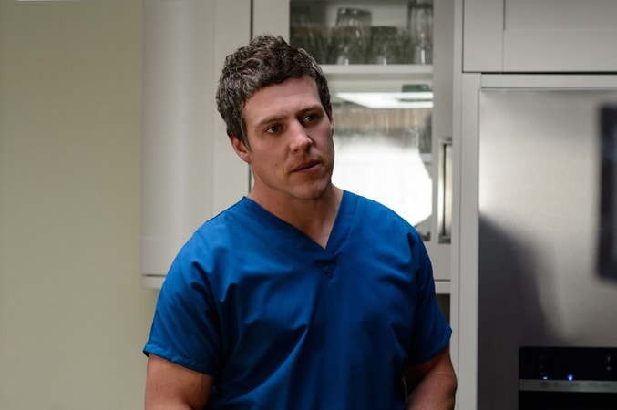 STEPHEN PEACOCKE as Nathan wearing hospital scrubs.