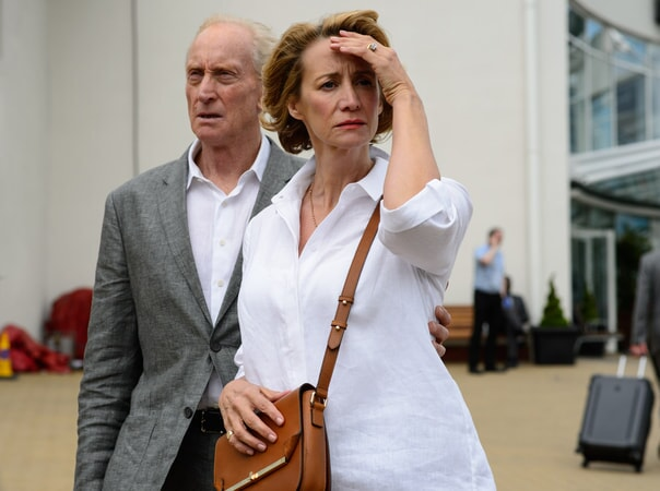 CHARLES DANCE as Stephen Traynor standing behind JANET McTEER as Camilla Traynor looking upset.