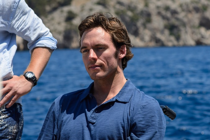 SAM CLAFLIN as Will Traynor with blue shirt and ocean in the background.