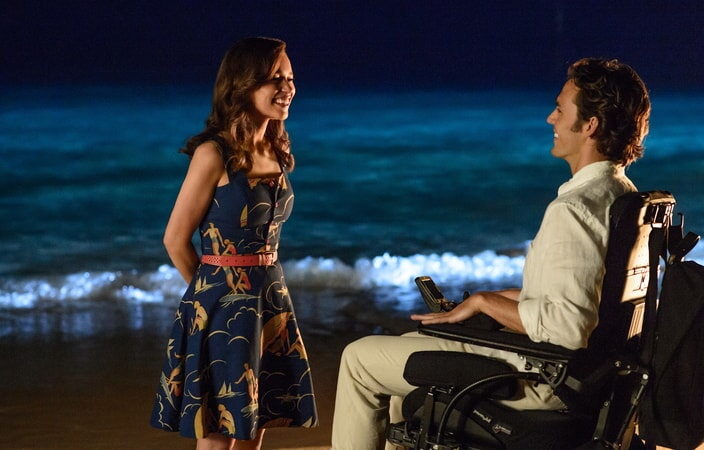 EMILIA CLARKE as Lou Clark and SAM CLAFLIN as Will Traynor smiling at each other on a beach at night.