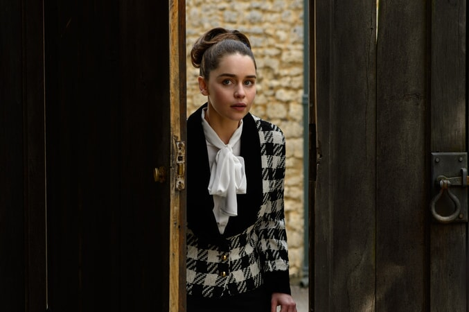 EMILIA CLARKE as Lou Clark wearing a plaid black and white dress coat.