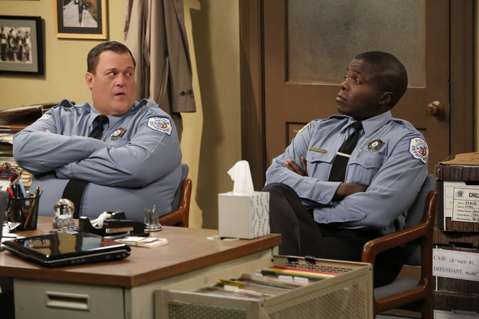Mike and Carl in police officer's uniform, sitting at desk, staring at each other (Season 6)