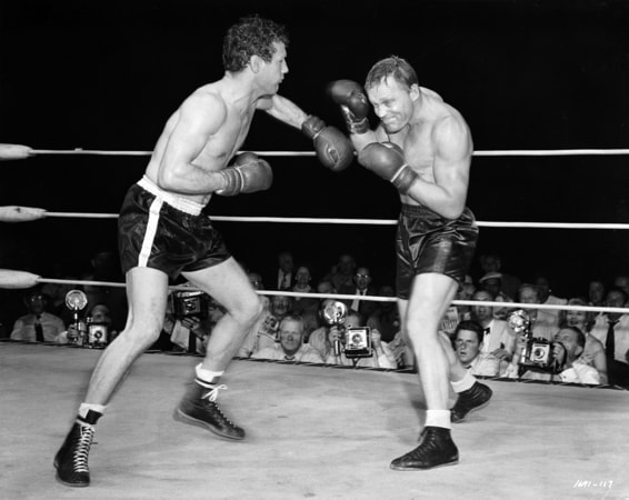 Full shot in boxing ring of Paul Newman, left, hitting Court Sheppard as Tony Zale, both wearing boxing gloves.