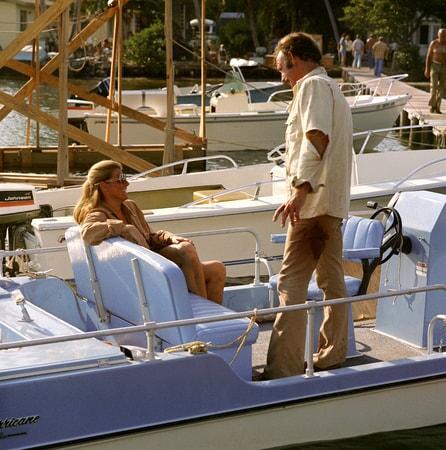 Jennifer Warren as Paula (seated) and Gene Hackman as Harry Moseby on boat.