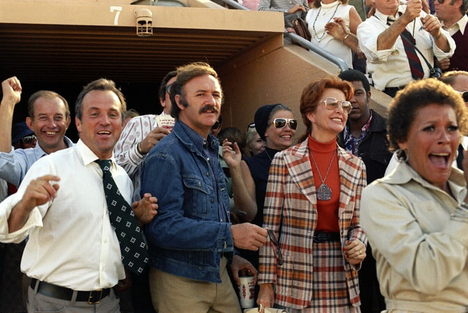 Gene Hackman as Harry Moseby in crowd at football game.