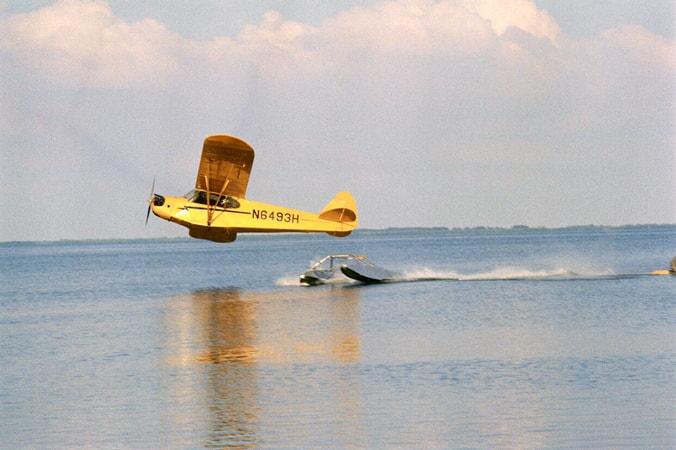 Wide shot of plane losing landing gear over ocean.