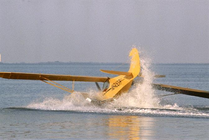 Full shot of plane crash-landing on ocean.