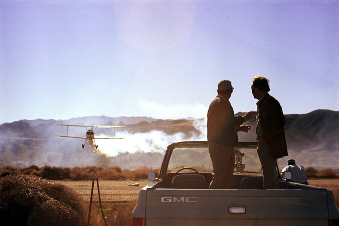 silhouetted shot of Gene Hackman as Harry Moseby and Ed Binns as Joey Ziegler standing on truck bed watching plane in distance.